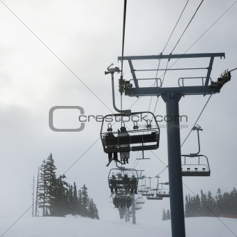 Skiers on chairlift.