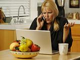 Woman Using Laptop & Cell Phone
