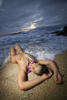 Nude woman lying on beach.