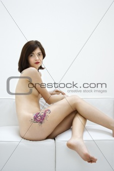 Nude young tattooed woman.