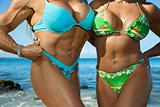 Women bodybuilders at beach.