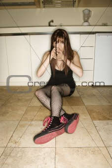 Woman sitting in kitchen.