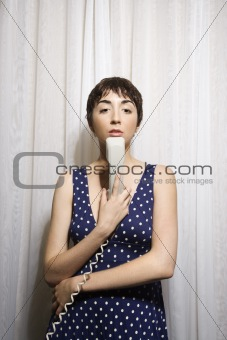 Woman holding telephone.