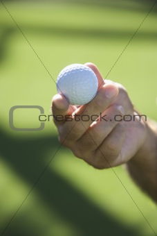 Hand holding golf ball.