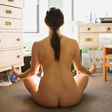 Nude woman meditating.