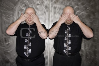 Twin men covering eyes.