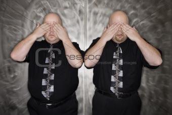 Twin men covering eyes.