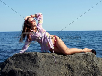 The sexual girl lays on a rock and looks at the sun