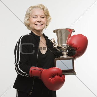 Senior woman with boxing trophy.