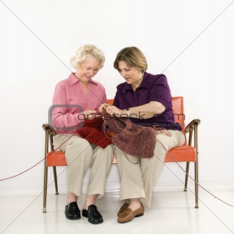 Two women knitting.
