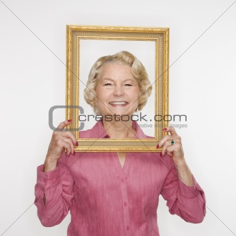 Woman holding picture frame.
