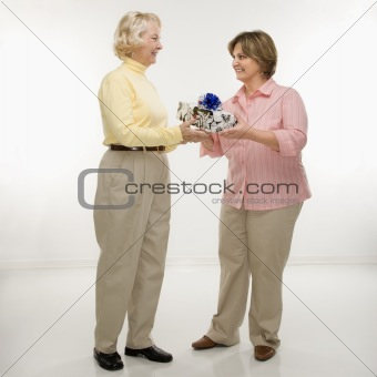 Woman giving gift to friend.