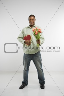 Man holding heart and flowers.