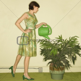 Woman watering plant.