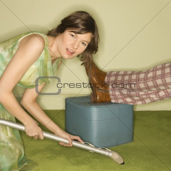 Woman vacuuming rug.