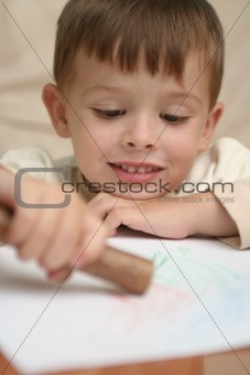 A smiling boy draws behind a table