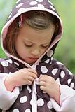 Child Putting on Raincoat