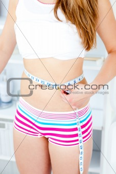 Caucasian woman mesuring her body