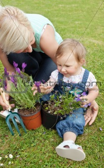 Beautiful mother showing her daughter a purple flower