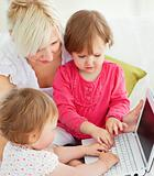 Cheerful family having fun with a laptop in the living-room 