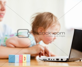 Cute woman surfing on the internet with her girl in the living-r