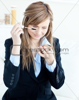 Beautiful businesswoman put her eye makupe-up on