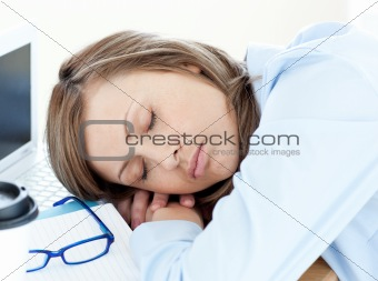 Tired businesswoman sleeping on her desk