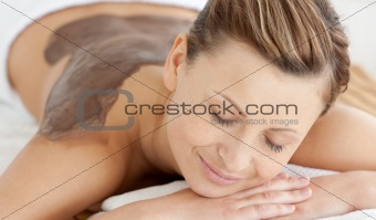 Charming woman enjoying a mud skin treatment