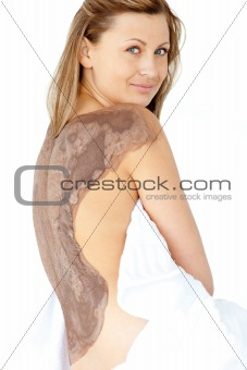 Attractive woman enjoying a mud skin treatment