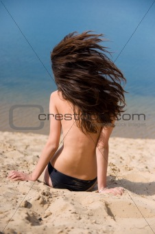 beautiful brunette on  beach sunbathes