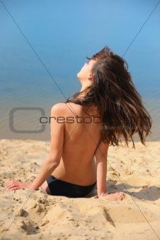 beautiful brunette on  beach sunbathes topless