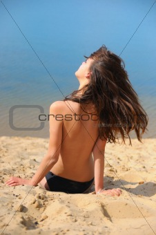 beautiful brunette on  beach sunbathes topless