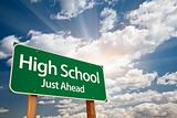 High School Just Ahead Green Road Sign with Dramatic Clouds, Sun Rays and Sky.