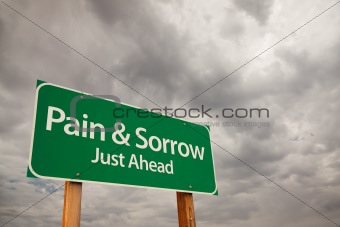 Pain and Sorrow Just Ahead Green Road Sign with Dramatic Storm Clouds and Sky.