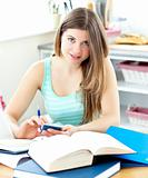 Smiling female teenager studying in the kitchen