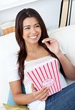 Woman sitting on sofa and eating popcorn