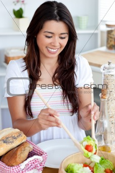 Young female woman preparing salad in kitchen