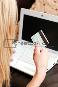 Blond woman lies on sofa and works at laptop