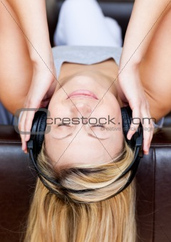 Sleeping woman lies on a sofa and listen music