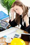 Stressed businesswoman sitting in her office in front of the tab
