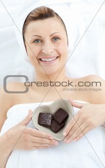 Cheerful woman holding a bowl in the shape of a heart with choco