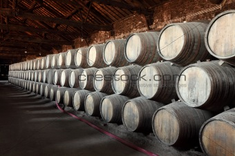 Old wine cellar full of wooden barrels