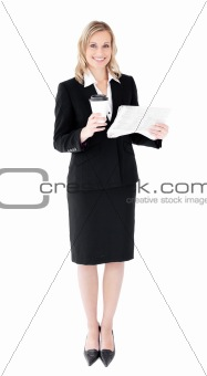 A beautiful businesswoman holding a cup of coffee reading a news