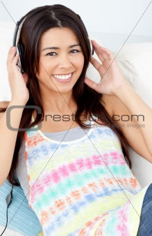 Jolly woman with headphones on lying on a sofa