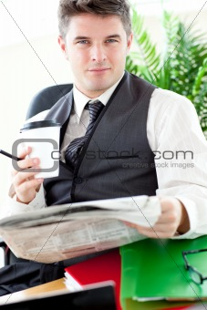 Serious businessman drinking a coffee while reading a newspaper 