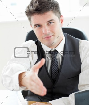 Charming  young businessman holding out his hand