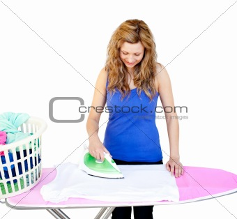 Glowing woman ironing her clothes on a ironing board