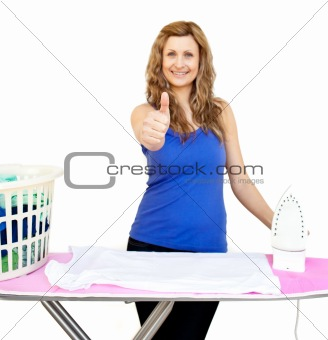 Handsome woman standing behind an ironing board with thumbs up