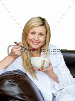 Charming woman eating cereals on the sofa