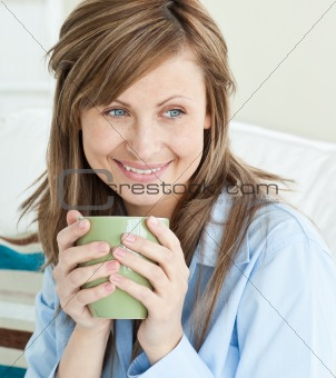 Beautiful woman holding a cup looking to the side